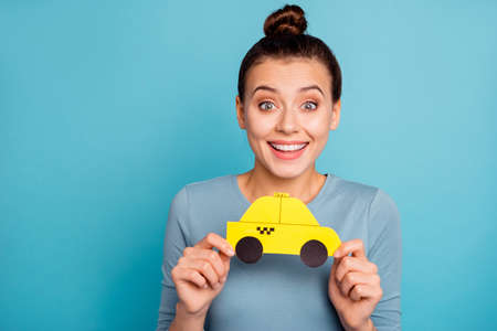 Portrait positive cheerful satisfied lady enjoy rejoice stylish trendy  top-knot astonished incredible news isolated blue background wow unbelievable hold hand paper card yellow car shirt modern