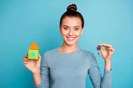 Close up photo of nice cute attractive lady real estate agent hold hand keys paper card condo satisfied content enjoy wear modern cotton outfit isolated on vivid background 版權商用圖片
