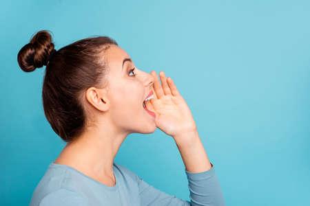 Profiel zijaanzicht foto van grappige funky tiener tiener schreeuwen luid advertenties nieuwigheden plaats hand in de buurt van open mond schreeuwen opzoeken geklede moderne jongere kleding geïsoleerd op blauwe achtergrond