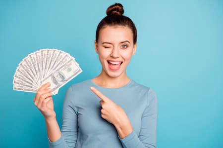 Portrait positive cheerful content student top-knot beautiful hold hand banknotes millionaire cash fun funky advise ads choice decision present casino trendy stylish sweater isolated blue background Stock fotó
