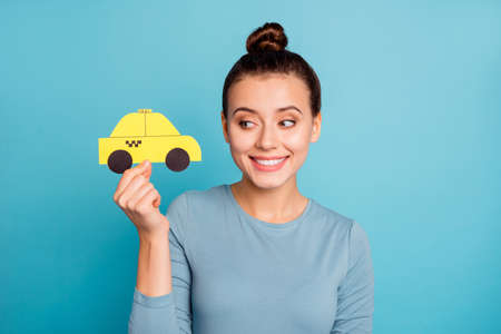 Portrait of nice charming beautiful top-knot lady hold hand paper car yellow taxi cab look show gesture glad positive cheerful satisfied wear cotton outfit shirt isolated on blue background