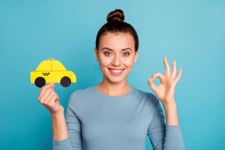Close up photo top-knot positive satisfied cheerful hipster advertise choose advert feedback hold hand paper card yellow taxi car cab route trendy stylish beautiful shirt isolated blue background