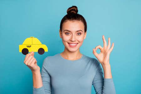 Nahaufnahme Foto Top-Knoten positiv zufrieden fröhlich Hipster Werbung wählen Anzeige Feedback halten Hand Papierkarte gelbes Taxi Auto Taxi Route trendiges stilvolles schönes Hemd isoliert blauer Hintergrund Standard-Bild