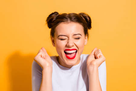 Close-up portrait of her she nice attractive fascinating lovely cheerful cheery crazy glam girl holding fists hope luck great success isolated over bright vivid shine yellow background