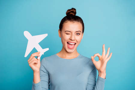 Close up photo beautiful she her lady hands arms paper airplane go abroad first time wink eye advising customers okey symbol use airline wear casual sweater pullover isolated blue bright background Stock Photo