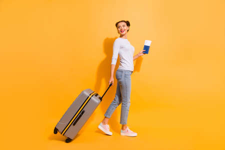 Profile side full length body size photo of cute lady going perfect voyage abroad explore sightseeing holding suit-case documents hands isolated yellow shadow background in white denim jeans clothes