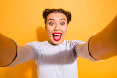 Close up photo of cute funny cheerful shocked childish lady taking photos impressed by incredible news with positive mood has her mouth open dressed in white sweater isolated over yellow background Reklamní fotografie