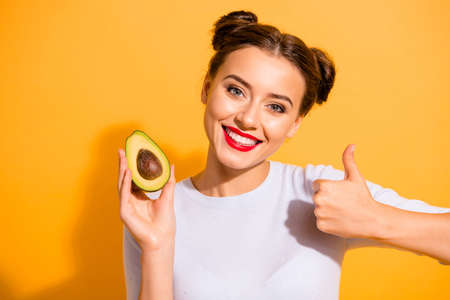 Close up photo beautiful she her lady pretty hairdo hold slice avocado show thumb up advising use user buy buyer new oil extract cream wear casual white pullover clothes isolated yellow background