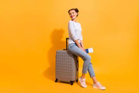Foto de perfil lateral de cuerpo entero del tamaño del cuerpo de una linda joven encantadora con ropa de mezclilla ligera de pie en la cola para su jet sentado en una maleta con documentos sobre fondo vivo