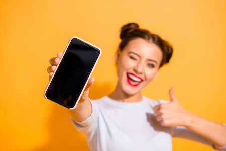Nahaufnahme einer funky energischen Studentin, die ihre Anerkennung der Handyvereinbarung in einem leichten Baumwolloutfit auf buntem Hintergrund zeigt Standard-Bild