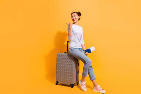 Full length side profile body size photo beautiful hairdo she her lady go abroad flight documents advising airport service wear casual jeans denim pullover sit big trolley isolated yellow background