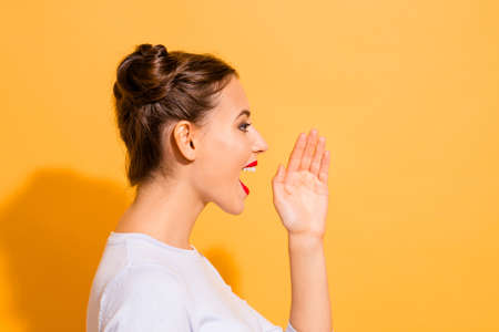 Profile side view close up photo of young attractive nice lady sharing incredible news about her life. She is raising her hand opening mouth isolated over vivid background in white clothes 写真素材