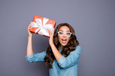 Close-up portrait of  nice lovely sweet winsome attractive cheerful cheery optimistic wavy-haired lady holding in hands cool red bow ribbon box isolated over gray pastel background. Standard-Bild - 147823247