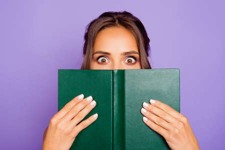 Close-up photo portrait of pretty sweet lovely smart clever cute wondered charming bookworm closing covering face with notebook notepad holding hands isolated violet background Фото со стока