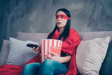 Close up photo beautiful she her superpower lady costume hold popcorn container controller change channels scary movie brave but fear wear red eye mask mantle sit sofa couch divan house indoors