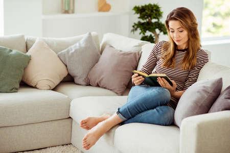 Portret jej ładnie wyglądającej uroczej samotnej atrakcyjnej falistej dziewczyny siedzącej na kanapie samotnie czytającej wiersze w jasnym białym wnętrzu pokoju