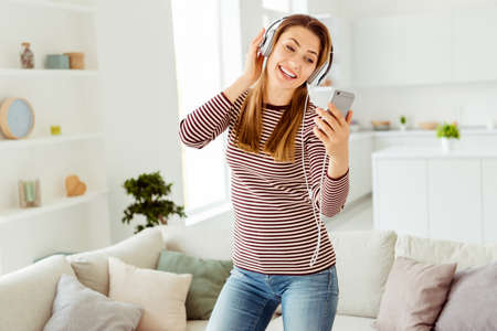 Close up photo beautiful she her lady arms hands hold telephone read words song earflaps ears overjoyed funky wear jeans denim striped pullover clothes bright comfort flat house living room indoors Stock Photo