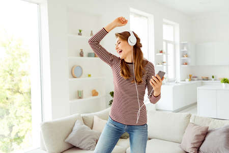 Portrait crazy funny funky hipster positive cheerful beautiful listen to sound tracks have head set feel satisfied content wear trendy striped shirt modern jeans have long curly wavy hair living room Imagens
