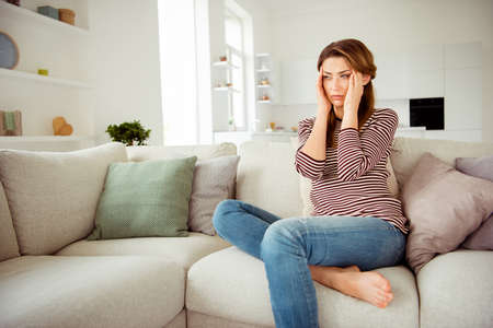 Close up side profile photo beautiful she her lady arms hold head look side terrible suffer pain displeased wear jeans denim striped pullover clothes sit comfort divan flat house living room indoors