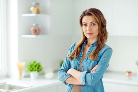 Close-up portrait of her she nice-looking lovely attractive content brown-haired lady housekeeper crossed arms in light white interior style kitchen Banque d'images