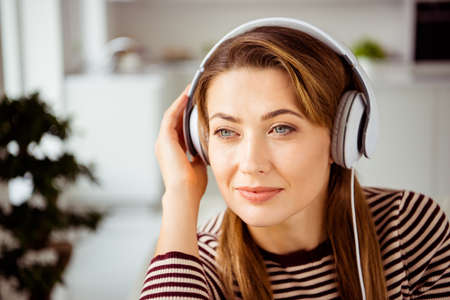 Close up photo of cute attractive lady student have holidays hear favorite soundtrack touch have headset feel glad wear modern striped shirt in living room
