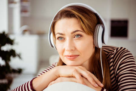 Close up photo of attractive nice cute youngster student have vacation holidays use headset listen soundtracks feel content dressed in striped shirt outfit in apartment 写真素材