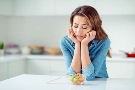 Close-up portrait of her she nice lovely charming attractive sad bored dull disappointed brown-haired lady looking at new green detox vitamin salad in light white interior style kitchen