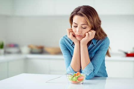 Close-up portret van haar, mooie, charmante, aantrekkelijke, verdrietige, saaie, saaie, teleurgestelde, bruinharige dame die kijkt naar nieuwe groene detox-vitaminesalade in een lichtwitte keuken in een interieurstijl