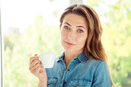 Close-up portrait of her se nice-looking lovely attractive charming cute well-groomed calm brown-haired lady holding in hand cup in light white interior style room