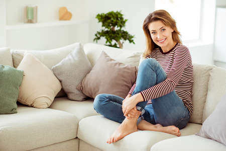 Full length side profile body size photo beautiful she her lady calm hold hands arms pretty long legs wear casual jeans denim striped pullover clothes sit comfort cozy divan house living room indoors