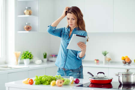 Portrait of her she nice lovely attractive confused brown-haired lady thinking how to prepare fresh hot dish meal dinner lunch green eco delicacy in light white interior style kitchen Banco de Imagens