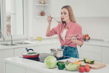 Close up photo beautiful she her lady prepare delicious dish meal try taste salty blow air making warm bring to mouth wear domestic home apparel shirt jeans denim outfit bright home kitchen indoors