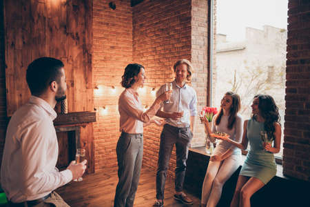 Company of nice attractive pretty elegant classy chic cheerful guys ladies having fun talk romantic atmosphere every year tradition in fashionable wood brick industrial loft interior room indoors Stock Photo