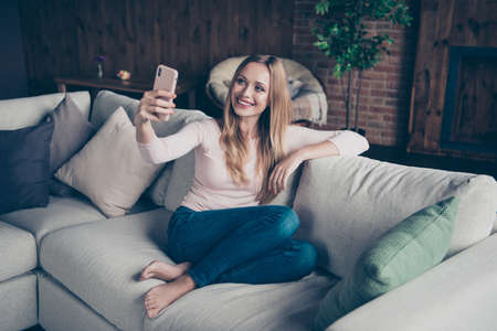 Photo portrait of attractive cheerful calm positive optimistic charming she her lady using telephone having blog sitting on divan without shoes 스톡 콘텐츠