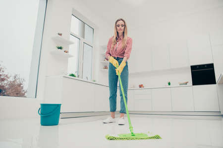 Full length body size photo beautiful busy nice duties she her lady wash white floor carefully look down not hurry housemaid wear jeans denim casual plaid checkered shirt bright light kitchen