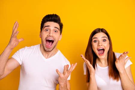 Cerrar foto funky increíble ella ella él él su pareja manos brazos levantados aire gritar increíble suerte suerte animadora partido de fútbol vestir casual camisetas blancas traje aislado fondo amarillo