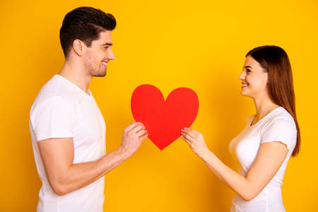 Close up side profile photo amazing beautiful she her he him his guy lady look eyes lovely hold hands arms big paper heart figure postcard wear casual white t-shirts isolated yellow background