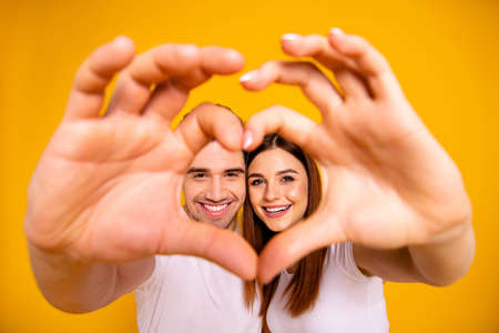 Close up photo amazing she her he him his guy lady hands arms fingers make heart figure faces inside form married spouse romance mood wear casual white t-shirts outfit isolated yellow background Banque d'images