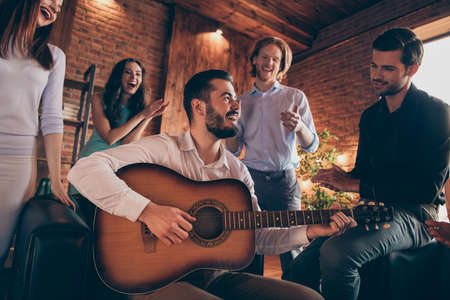 Close up photo gathering best friends buddies hang out vocal soloist play guitar old beloved songs legends she her ladies he him his guys wear dresses shirts formal wear sit sofa loft room indoors