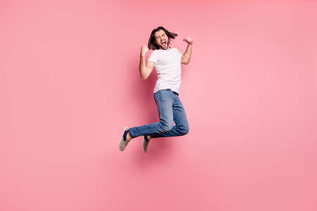 Full length side profile body size photo handsome he him his macho yelling loud jump air raise arms hands excited football competition wear casual white t-shirts denim jeans isolated pink background 写真素材