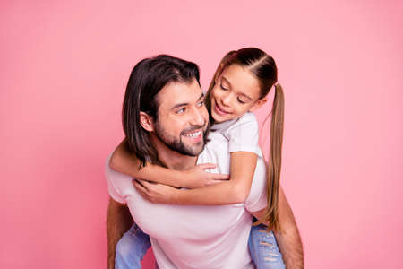 Close up photo beautiful adorable she her little lady he him his daddy dad hold little princess piggyback hands arms funny funky wear casual white t-shirts denim jeans isolated pink bright background