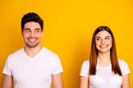 Close up photo two amazing beautiful she her he him his couple standing side by side look each other did trick funky childish mood wear casual white t-shirts outfit clothes isolated yellow background Stock fotó