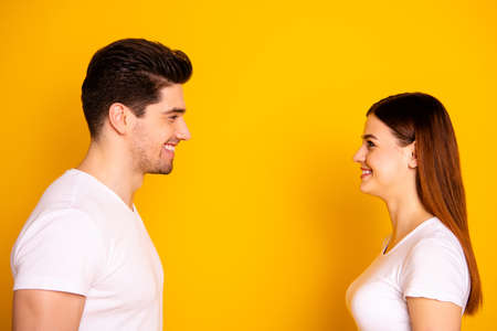 Close up side profile photo funny amazing beautiful she her he him his guy lady laugh laughter stand opposite wait first who take eyes off wear casual white t-shirts outfit isolated yellow background Banco de Imagens - 122177544
