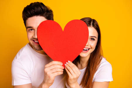 Close up photo beautiful she her he him his guy lady hiding facial expression laugh laughter hold hands arms heart shape paper postcard in love wear casual white t-shirts isolated yellow background