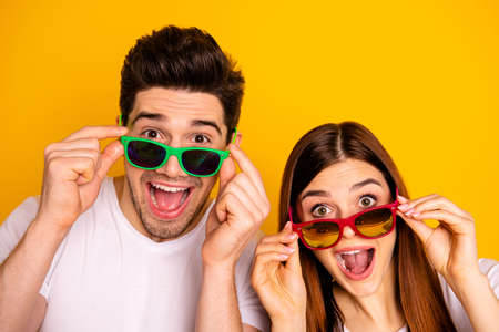 Close-up portrait of his he her she two nice attractive lovely charming stylish trendy cheerful cheery people opened mouth isolated over vivid shine bright yellow background