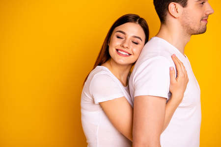 Close up side profile photo beautiful she her he him his guy lady pair hold tight close hands arms husband strong back eyes closed emotional wear casual white t-shirts isolated yellow background Imagens