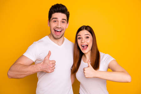 Close up photo funky funny amazing she her he him his model guy lady hands arms thumb fingers raised air advise product buy buyer approve wear casual white t-shirts outfit isolated yellow background