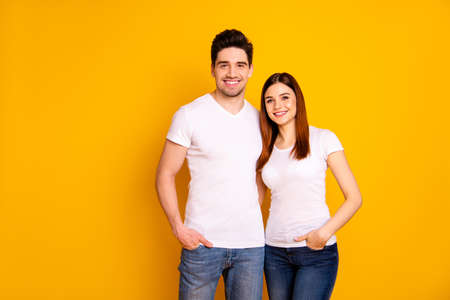 Close up photo funny amazing beautiful she her he him his guy lady standing hugging sincere beaming smile easy-going best fellows buddies wear casual white t-shirts outfit isolated yellow background