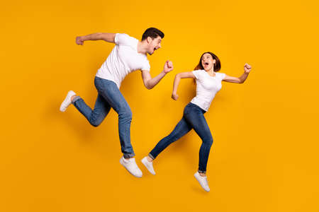 Full length side profile body size photo funky she her he him his pair jumping high hurry shopping raised fists yell scream shout loud wear casual jeans denim white t-shirts isolated yellow background Stock fotó