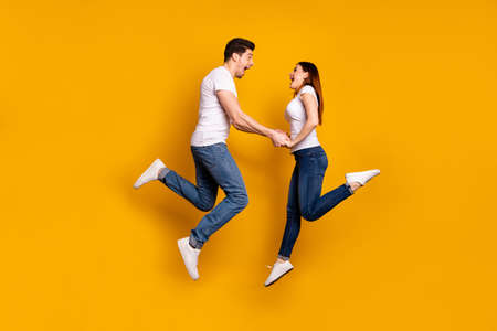 Full length side profile body size photo funky crazy she her he him his pair touch arms jumping high yell scream shout best buddies wear casual jeans denim white t-shirts isolated yellow background